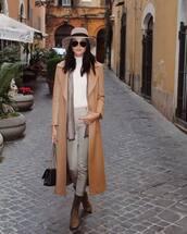 coat,long coat,beige,brown boots,skinny pants,bag,white turtleneck top,scarf,sunglasses,hat