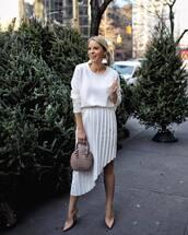 skirt,midi skirt,pleated skirt,asymmetrical skirt,high heel pumps,white top,long sleeves,handbag,earrings