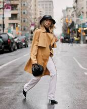 coat,trench coat,black boots,heel boots,white pants,flare pants,black bag,handbag,black sweater,turtleneck sweater,bucket hat