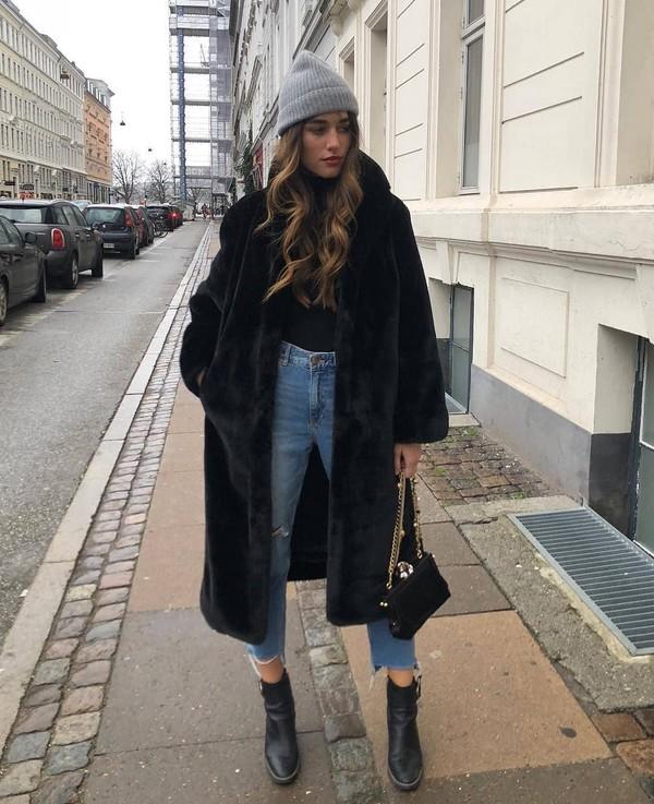 coat faux fur coat long coat cropped jeans straight jeans black bag black turtleneck top knit hat ankle boots black boots black coat beanie