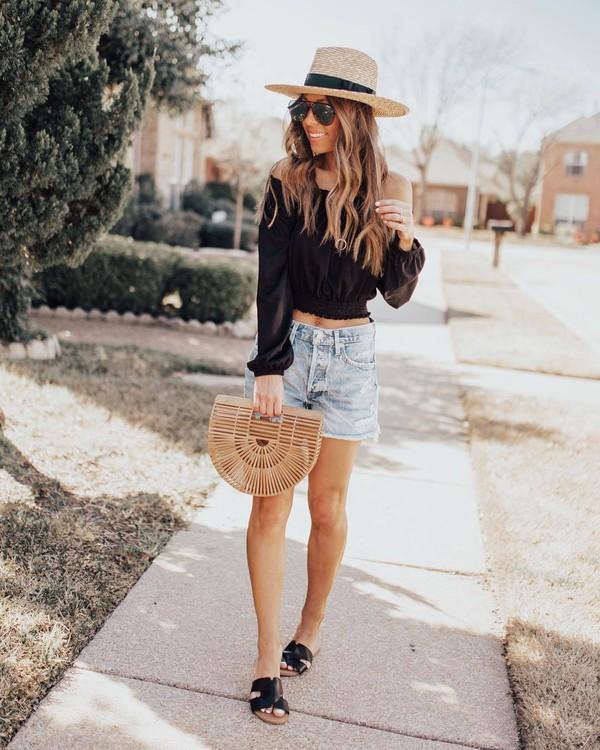 top black top off the shoulder top denim shorts flat sandals wood handbag hat