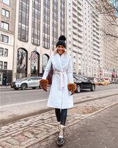 hat,black beanie,white coat,black leggings,ankle boots,gloves,bag
