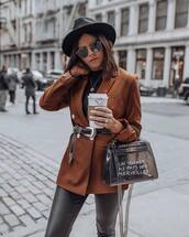 jacket,blazer,double breasted,brown,black belt,black leather pants,pvc,bag,black turtleneck top,hat