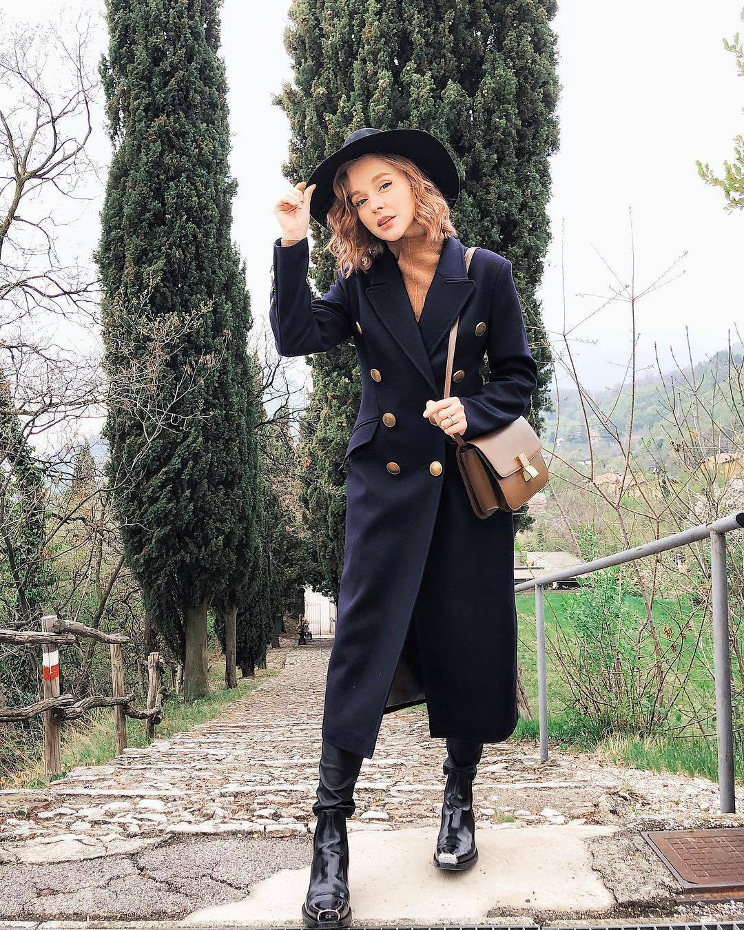 coat long coat double breasted black boots ankle boots black pants leather pants brown bag turtleneck sweater hat