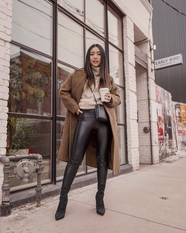 pants black leather leggings black boots sock boots beige coat turtleneck sweater black bag