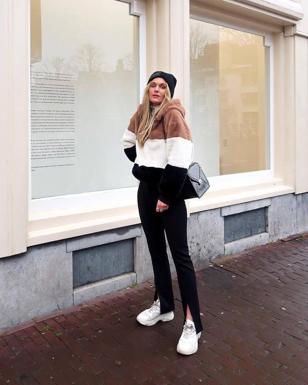sweater hoodie faux fur stripes white sneakers black pants slit pants black bag black beanie