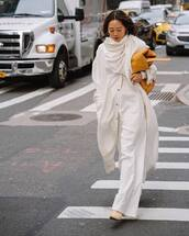bag,yellow bag,suede bag,white coat,long coat,white pants,wide-leg pants,white top,scarf,heel boots