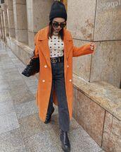 coat,long coat,orange coat,black jeans,straight jeans,black boots,top,black bag,beanie