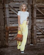 top,white t-shirt,high waisted pants,yellow pants,brown bag,black sneakers,wide-leg pants