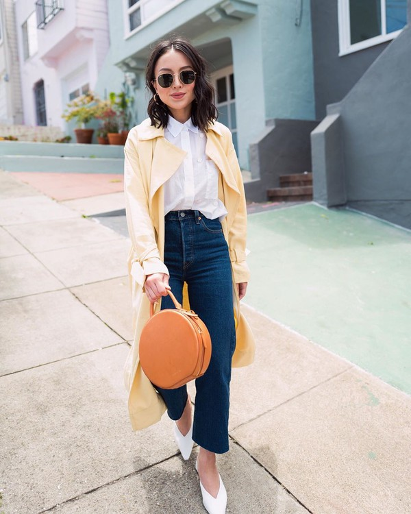 coat trench coat yellow coat long coat white shirt high waisted jeans flare jeans brown bag mules