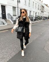 coat,faux fur vest,black leather pants,white sneakers,black bag,white sweater