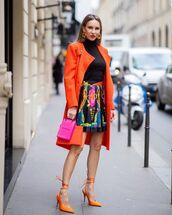 coat,orange coat,slide shoes,pleated skirt,mini skirt,bag,black turtleneck top