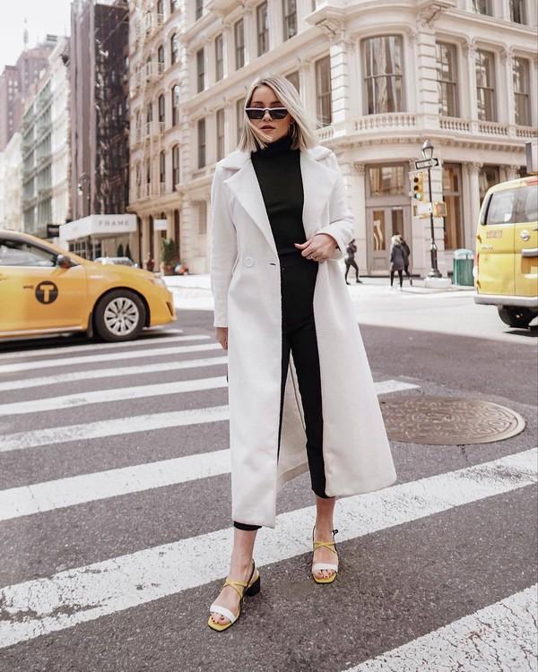 coat white coat long coat black turtleneck top black skinny jeans sandals