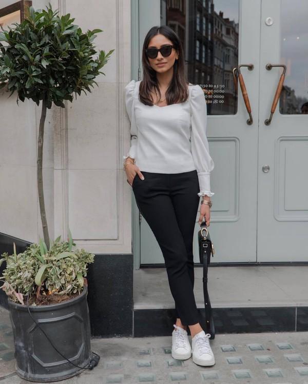 top white blouse long sleeves black pants skinny pants white sneakers black bag