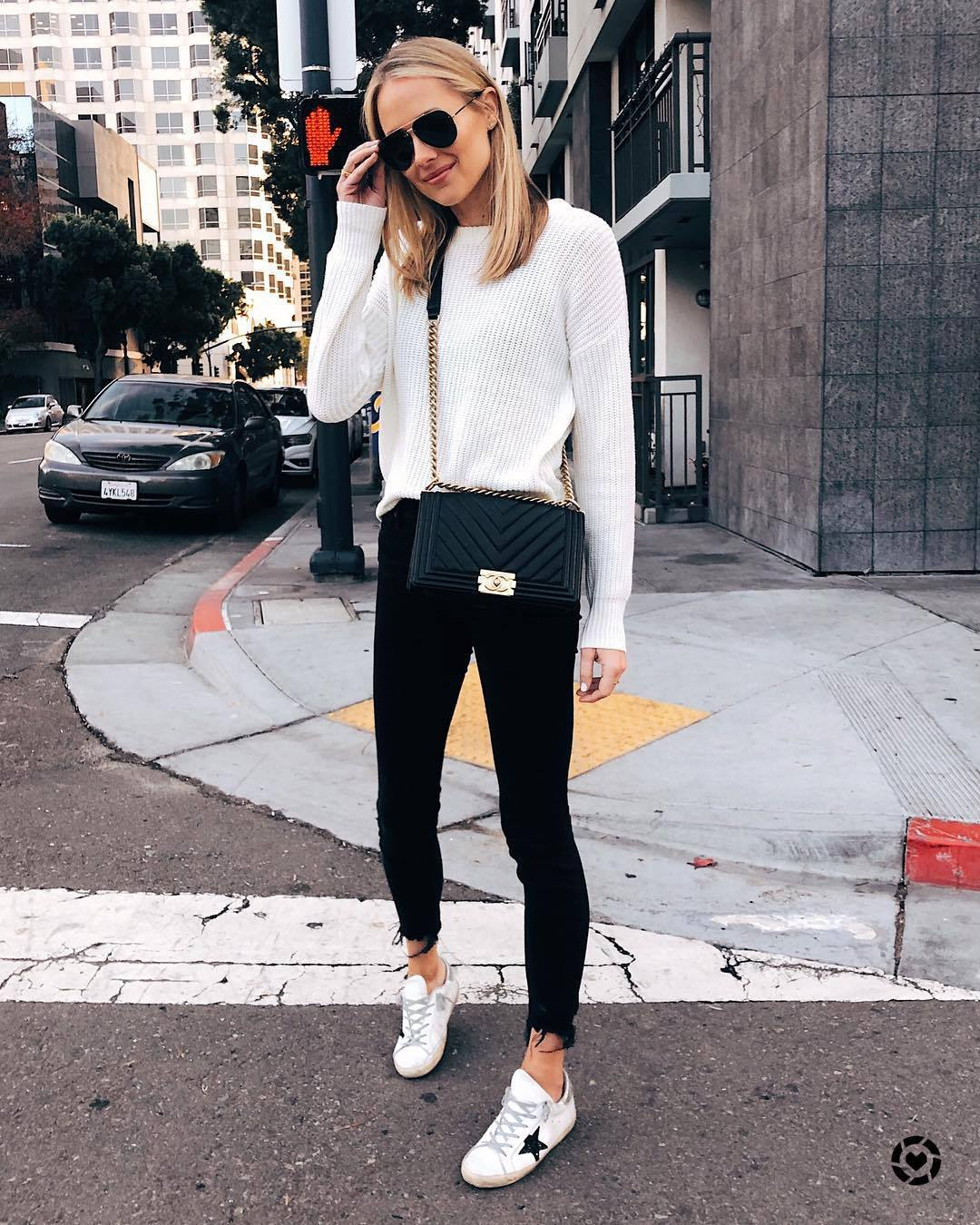 sweater white sweater knitted sweater white sneakers black skinny jeans cropped jeans black bag crossbody bag sunglasses streetstyle