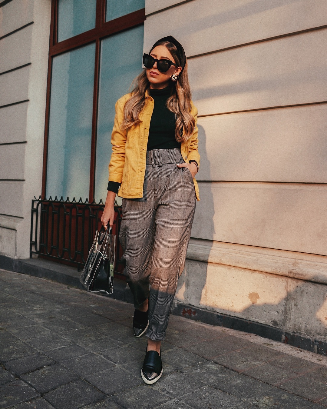 jacket denim jacket yellow jacket black shoes plaid high waisted pants grey pants black bag pvc handbag black turtleneck top