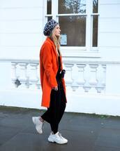 coat,orange coat,white sneakers,black pants,black belt,black sweater,leopard print,beret