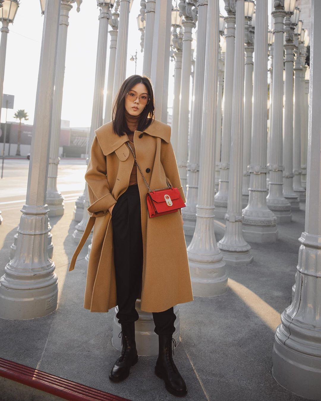 bag red bag long coat black boots black pants pleated pants. turtleneck sweater