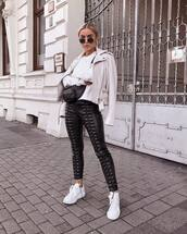 pants,black leather pants,lace up,white sneakers,sweatshirt,leather jacket,belt bag