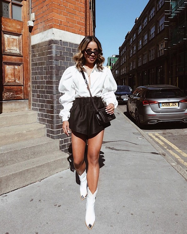 top white shirt puffed sleeves black shorts leather shorts white boots black bag
