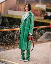 bag,handbag,green coat,vinyl,pleated,pants,white boots,turtleneck sweater