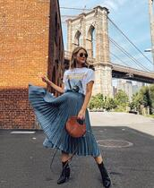 bag,brown bag,round bag,pleated skirt,ankle boots,white t-shirt