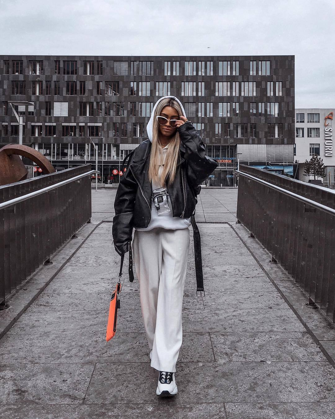 jacket leather jacket oversized jacket black jacket white pants wide-leg pants white sneakers white hoodie orange bag prada